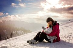 Young mother, breastfeeding her baby boy on top of mountain on s. Unset in Austrian Alps, beautiful scenery landscape Stock Images