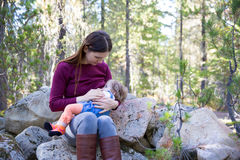 Young mother breastfeeding her baby outdoors. Young mother breastfeeding her baby in nature outdoors, sitting on big rocks in the forest Stock Images