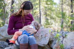 Young mother breastfeeding her baby outdoors. Young mother breastfeeding her baby in nature outdoors, sitting on big rocks in the forest Royalty Free Stock Images