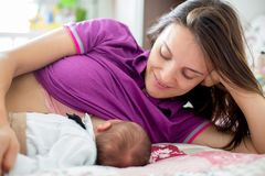 Young mother breastfeeding  her newborn baby boy. At home Stock Images