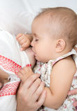 Young mother breastfeeds her baby. Royalty Free Stock Photo