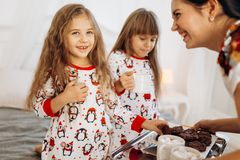 Young mother is bringing cocoa with Marshmallows and cookies to her daughters in pajamas sitting on the bed in the full stock photo