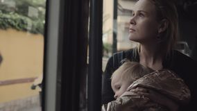 A young mother in a bus. A portrait of a young mother, travelling in a bus with a baby in her arms stock footage