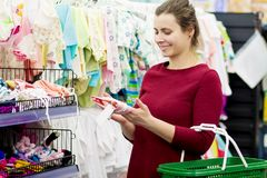 A young mother buys clothes for her baby in a children`s clothing store. The girl chooses clothes in the mall. Shopping clothing concept. Attractive woman Royalty Free Stock Images