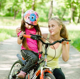 Young mother calms the sad daughter who did not get to ride a bike Stock Photography