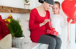 Young mother, cancer patient, and her cute daughter, celebrating return home from hospital. Welcome home or birthday party. Young mother, cancer patient, and Royalty Free Stock Images