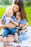 Young Mother cant calm the her twins. In a park stock photography