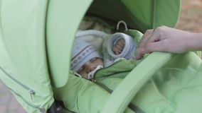 Young mother carefully look at the small child who sleeps in the stroller while walking in autumn park. stock video footage