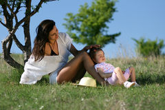 Young mother caring for her child. Young women loving her daughter, gently touching her head and having fun in nature Royalty Free Stock Photos