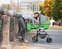 Young mother carrying baby in autumn park Royalty Free Stock Images