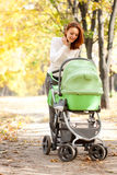 Young mother carrying baby in autumn park Royalty Free Stock Photography