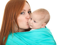Young mother carrying baby boy in sling Royalty Free Stock Image