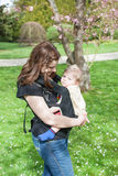 Young mother carrying baby son in rucksack in park Stock Photo