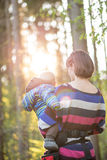 Young mother carrying her baby boy on a walk. Through a sunny forested area Royalty Free Stock Photography