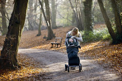 A young mother checking on her son in a stroller Royalty Free Stock Images
