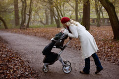 A young mother checking on her son in a stroller Royalty Free Stock Image