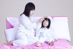 Young mother checks temperature her girl Royalty Free Stock Photography