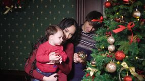 Young mother with chic black hair holding in his arms her little son, dressed in a sweater with a deer. Woman helping stock video footage