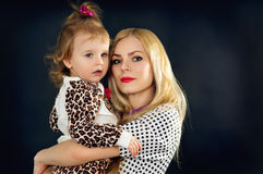 Young mother with a child on a black background in the studio Royalty Free Stock Image
