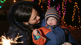 Young mother with a child celebrate the new year on the street with a sparkler. Hugging and smiling at the camera stock footage