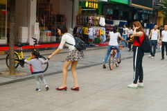 A young mother with a child in the commercial pedestrian street Royalty Free Stock Photography