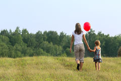 Young mother with the child goes across the field. Outdor. Stock Photos