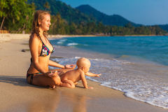 A young mother with a child having fun on a tropical beach.. Nat Royalty Free Stock Photo