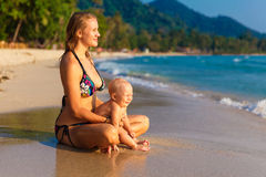 A young mother with a child having fun on a tropical beach.. Nat Royalty Free Stock Photography