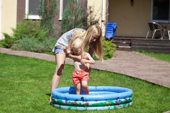 Young mother with a child near a rubber children's pool Royalty Free Stock Photo
