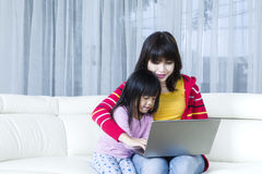 Young mother and child playing laptop Royalty Free Stock Photography