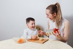 Young mother with a child is prepared in the kitchen. On white background royalty free stock photography