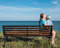 Young mother with child sitting on the bench near the sea ocean. Royalty Free Stock Photography