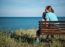 Young mother with child sitting on the bench near the sea ocean. Stock Photography
