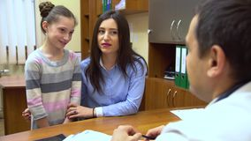 A young mother with a child to the doctor. The doctor gives the girl a therapeutic agent. stock video