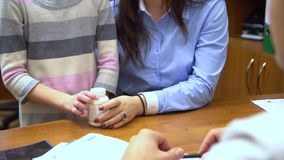 A young mother with a child to the doctor. The doctor gives the girl a therapeutic agent. stock footage