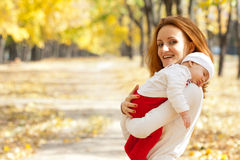 Young mother with child walking in autumn park Stock Photo