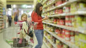 Young Mother and child walks along wholesale shelves and taking goods in shop trolley, woman stands near the supermarket. Shelf and selects the products for her stock video footage