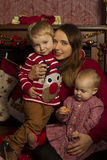Young mother with children by the fireplace in new year Stock Images