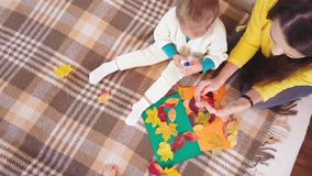 Young mother with children make autumn applique from autumn leaves. Little girl with mom glues autumn casting on a stock video