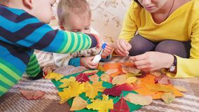 Young mother with children make autumn applique from autumn leaves. Little girl with mom glues autumn casting on a stock video footage