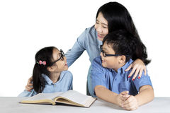 Young mother with children studying together. Image of young mother talking with her children while studying together in the studio Royalty Free Stock Photo