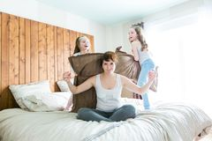 Young mother and childs on morning yoga exercises in bed. A Young mother and childs on morning yoga exercises in bed Royalty Free Stock Images