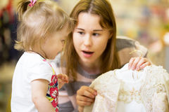 A young mother chooses a dress for her little daughter Royalty Free Stock Images