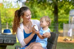 Young mother cleaning her young son after eating. Loving young mother cleaning her young son after eating as they sit together on a bench in a park with her royalty free stock photography