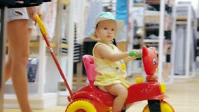 Young mother in clothing store with little daughter on childrens bicycle stock video footage