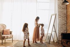 Young mother combing her little daughter`s hair standing in front of the mirror and her second daughter comes to them in stock photo