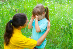 Young mother comforts her crying daughter Stock Photos
