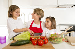 Young mother in cook apron and sweet beautiful twin daughters cooking preparing together salad Stock Photos