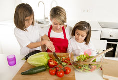 Young mother in cook apron and sweet beautiful twin daughters cooking preparing together salad Stock Photo