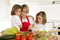 Young mother in cook apron and sweet beautiful twin daughters cooking preparing together salad Stock Image